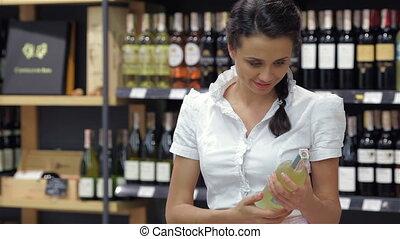 Portrait of pretty woman looking at wine bottle