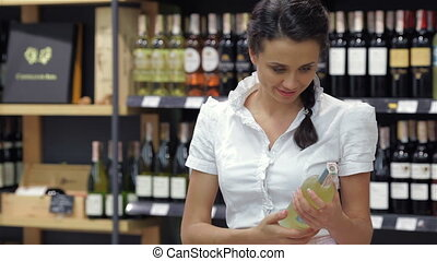 Portrait of pretty woman looking at wine bottle