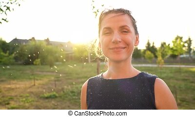 Portrait of smiling woman outdoors in sunny day. Fluff from reeds flies around