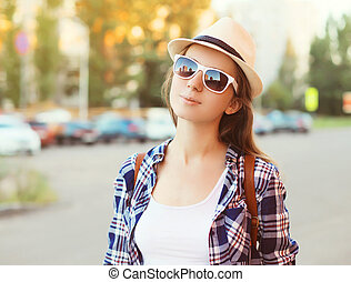 Portrait of pretty woman wearing a sunglasses and straw hat in summer day
