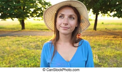 Portrait of pretty woman with hat outdoors in sunny day...