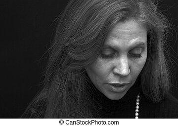 portrait of pretty woman with long hair and lashes in black and white with head down full lips and appears to be talking.