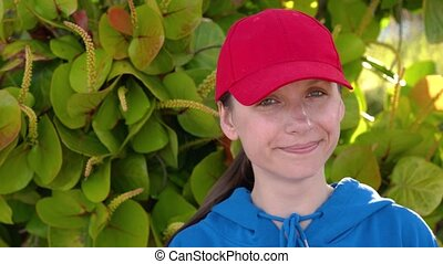 Portrait of pretty woman with red hat outdoors in sunny day...