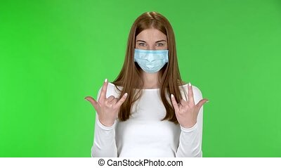 Portrait of pretty young girl in medical protective face mask looking at camera and making a rock gesture with both hands. Redhead with long straight hair in a white blouse on a green screen in the studio. Health Protection Corona Virus Concept.