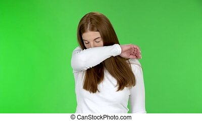 Portrait of pretty young girl is sneezes and covers itself with an elbow. Redhead with long straight hair in a white blouse on a green screen in the studio. Health Protection Corona Virus Concept.