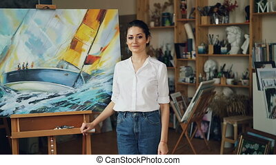 Portrait of pretty young lady painter looking at camera and...