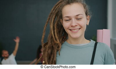 Portrait of pretty young lady with dreadlocks holding yoga ...