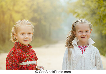 Portrait of pretty young sisters posing in park