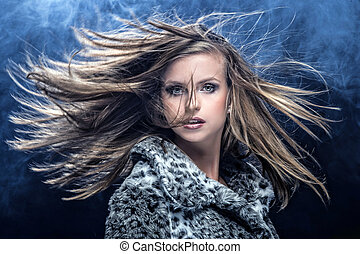 Portrait of pretty young woman flinging long blonde hair
