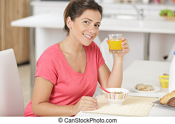 portrait of pretty young woman having breakfast at home