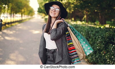 Portrait of pretty young woman holding paper bags standing outdoors in the city and looking at camera on sunny autumn day. Shopping, youth and street concept.