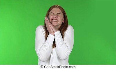 Portrait of pretty young woman is clapping her hands with wow happy joy. Redhead with long straight hair in a white blouse on a green screen in the studio.