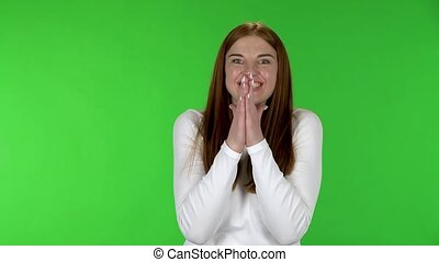 Portrait of pretty young woman with shocked and surprised wow face expression. Redhead with long straight hair in a white blouse on a green screen in the studio.