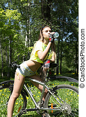 Portrait of pretty young woman with bicycle in a park - outdoor. girl drinks water from a bottle