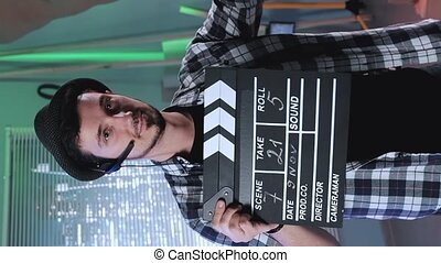 Portrait of producer assistant smiling to the camera and giving action with movie clapper board. In the background there are skyscrapers at night. Video with Vertical Screen Orientation 9:16