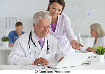 Portrait of professional doctors working in cabinet - ...