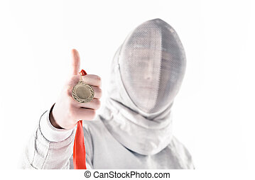 Portrait of professional fencer in fencing mask holding medal with thumb up on white