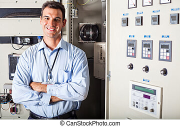 portrait of professional industrial technician in front of computerized machinery