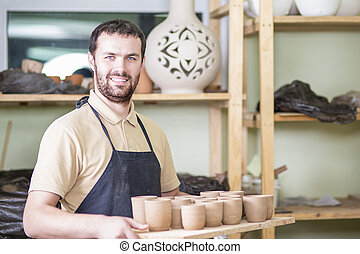 Portrait of Professional Male Ceramist Holding Tray with...