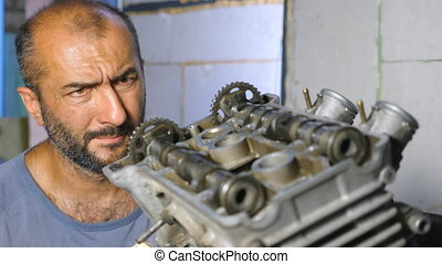 Portrait of professional mechanic repairing motor of vehicle. Attentive repairer fixing automobile engine. Auto master doing his work in garage or workshop. Man engaged servicing auto. Slow motion.
