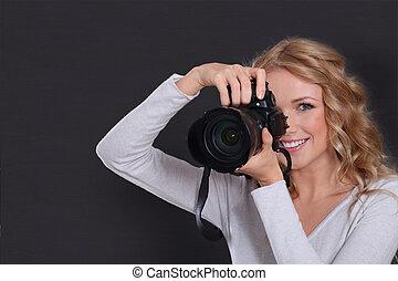 Portrait of professional photographer holding photo camera