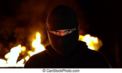 Portrait of protesting activist in mask against burning barricades at night. Concept of strikes, political conflicts and confrontation