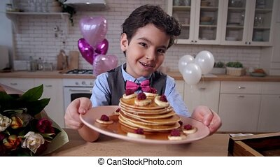 Portrait of proud boy with homemade pancakes