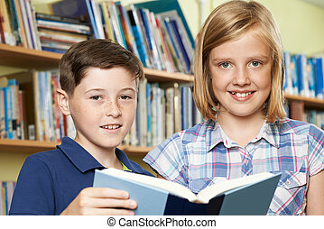 Portrait Of Pupils Reading Book In Library