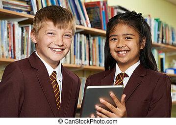 Portrait Of Pupils Wearing School Uniform Using Digital Tablet In Library
