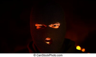 Portrait of rage ultras or protester in black mask during...