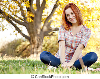 Portrait of red-haired girl in the autumn park.
