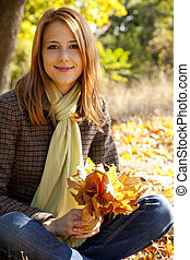 Portrait of red-haired girl in the autumn park