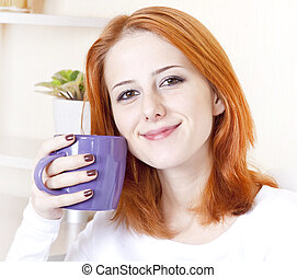 Portrait of red-haired girl with violet cup.