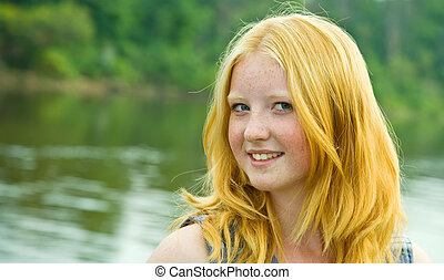Portrait of red-haired teenager girl against river