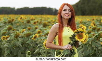 Portrait of red-haired woman in field of sunflowers