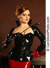 Powerful dominatrix type redhead woman wearing a latex jacket and skirt holding a riding crop in a strong stance.