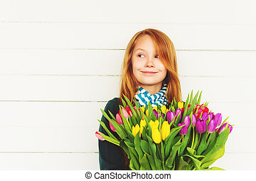 Portrait of redhead girl of 8-9 years old, holding bright bouquet of colorful fresh tulips, standing against white wooden background