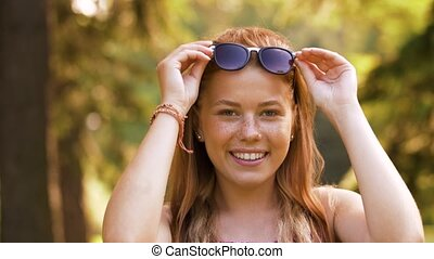 portrait of redhead teenage girl in summer park - people and...