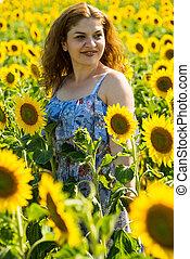 Portrait of redhead woman in sunflower field