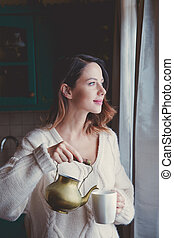 Portrait of redhead woman in sweater and cup