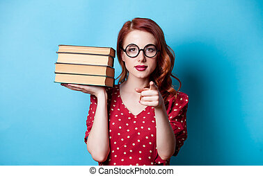 Portrait of redhead woman with books