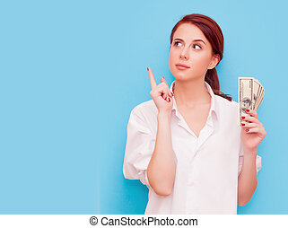 Portrait of redhead woman with money