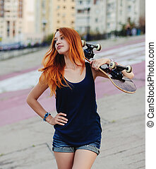 Portrait of redhead young girl with skateboard.