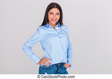 relaxed brunette woman wearing a blue shirt and jeans