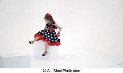 Relaxed barefoot girl in stylish clothes sitting on a white cube on a white background, cute preteen girl seriously looking at the camera