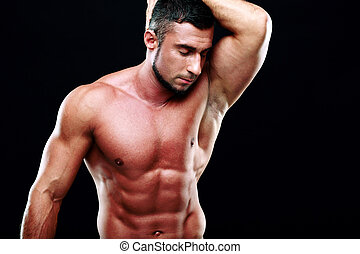 Portrait of relaxed muscular man with closed eyes over black background