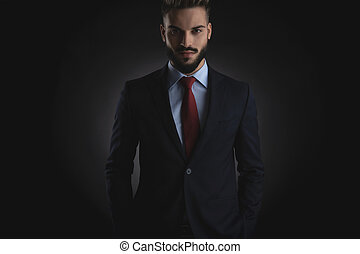 portrait of relaxed smart casual man standing with hands in pocket