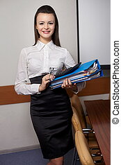 Portrait of relaxed young business woman smiling at office with documents