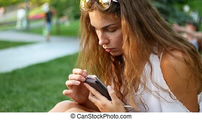 Portrait of relaxed young lady in a summer park reading a text message on her mobile phone.
