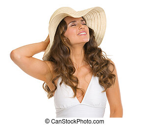 Portrait of relaxed young woman in swimsuit and hat